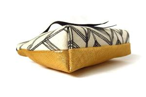 side view of gold leather and hand drawn canvas pouch with leather