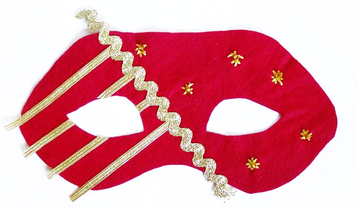 red felt mask with gold embellishments
