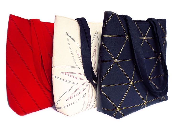 three 517 totes from Holland Cox, in red, black, and off-whiite